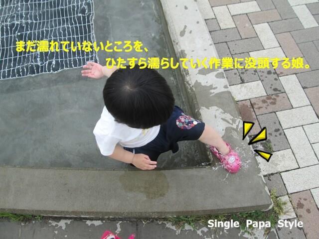 縁石を無言で濡らしていく作業をする娘